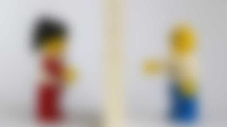 Lego people separated by lego wall