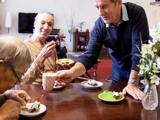 ouderen eten taart bij meer en oever