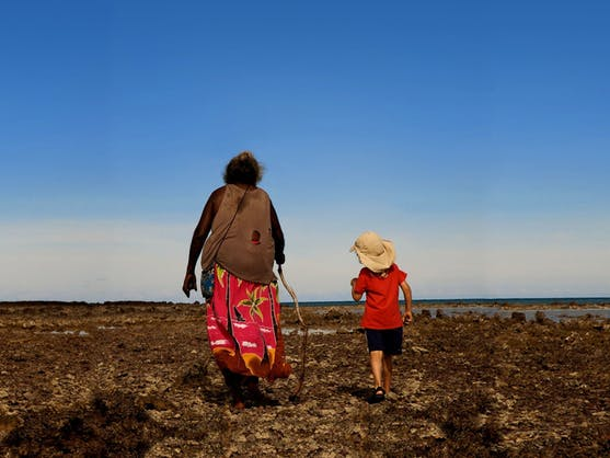 Aboriginal woman walking with a child. Scene in the Down To Earth documentary