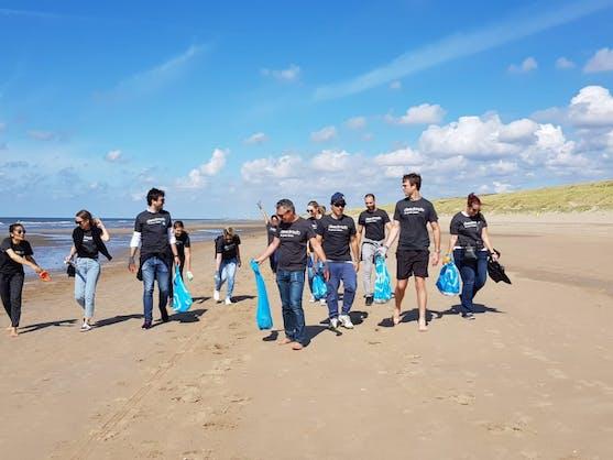 team corporate vrijwilligers zijn vuilnis aan het oprapen op het strand